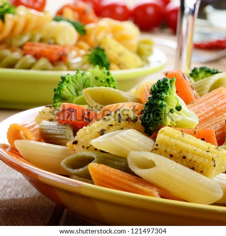 Pasta penne salad with broccoli, carrot and corn - stock photo