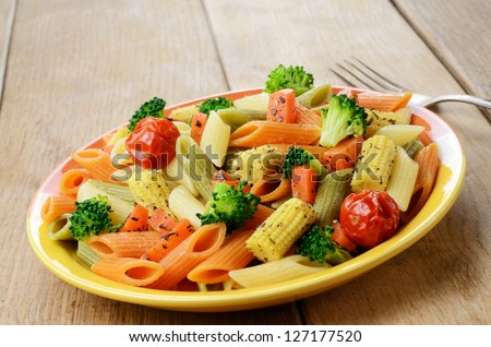 Pasta penne salad with broccoli, carrot, corn, and tomatoes on the wooden table - stock photo