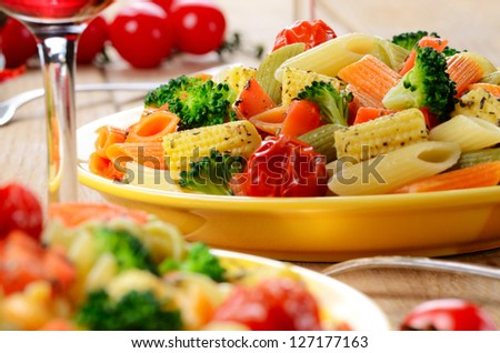 Pasta penne salad with broccoli, carrot, corn, served with red wine