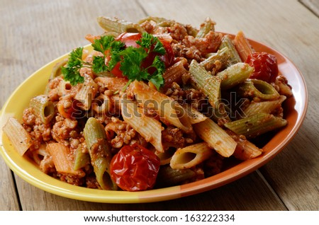 Pasta penne with homemade bolognese sauce on the kitchen table