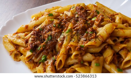 pasta penne with stew meat sauce in a plate on wooden table