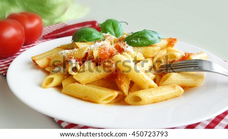 Pasta penne with tomato sauce mediterranean food background.