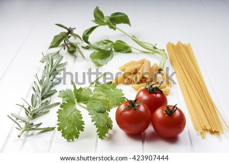 Pasta penne with tomatoes and basil on white table top - stock photo