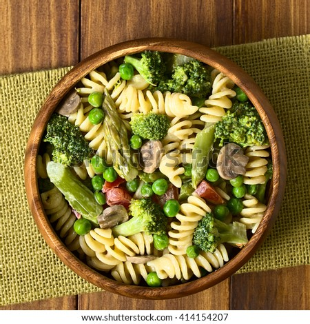 Pasta primavera with green asparagus, pea, broccoli, mushroom and tomato in cream sauce served in wooden bowl, photographed overhead with natural light