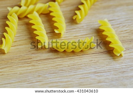 Pasta. Raw italian pasta on a wooden background. Italian pasta for your kids menu. Tasty fusilli pasta on wooden background. - stock photo