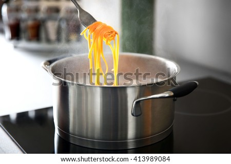Pasta rolled on fork over pan on stove in the kitchen - stock photo