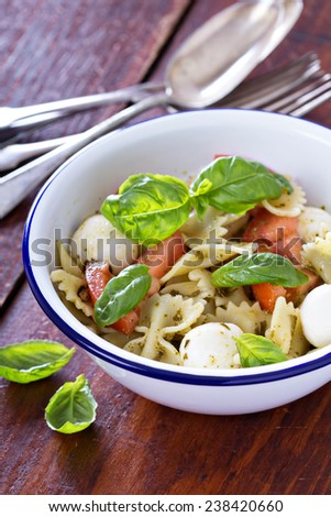 Pasta salad Caprese style with farfalle, tomato and mozarella - stock photo