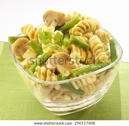 Pasta salad, green beans, mushrooms in transparent bowl - stock photo