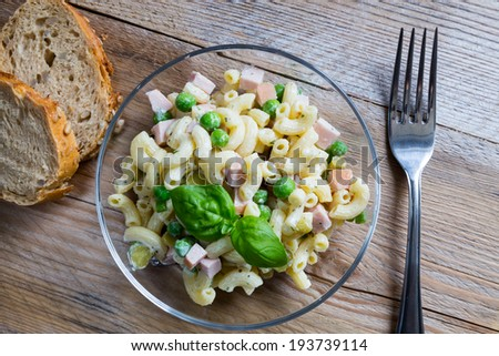 Pasta salad in a glass bowl on wood. - stock photo