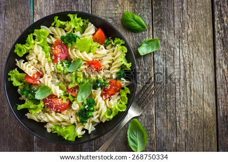 Pasta salad with cherry tomatoes and broccoli, top view - stock photo