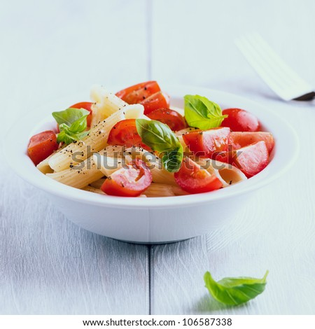 Pasta salad with cherry tomatoes and fresh basil - stock photo