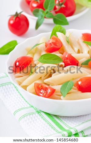 Pasta salad with cherry tomatoes and fresh basil leaves - stock photo