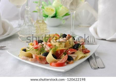Pasta salad with ham, tomato and olive sauce - stock photo