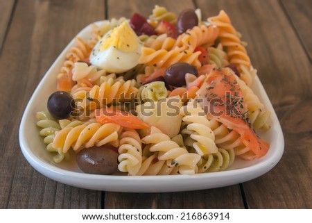 Pasta salad with olives, tomato, beetroot, cucumber, smoked salmon and boiled egg - stock photo