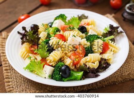 Pasta salad with tomato, broccoli, black olives,  and cheese feta - stock photo
