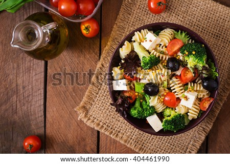 Pasta salad with tomato, broccoli, black olives,  and cheese feta. Top view - stock photo
