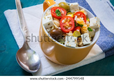 pasta salad with tomato rice and feta cheese on bowl - stock photo