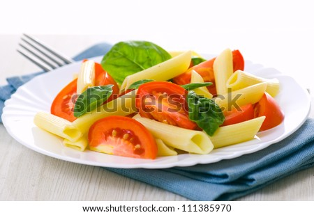 Pasta salad with tomatoes and fresh basil leaves - stock photo