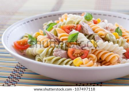 pasta salad with tuna, tomatoes, sweet corn and basil - stock photo
