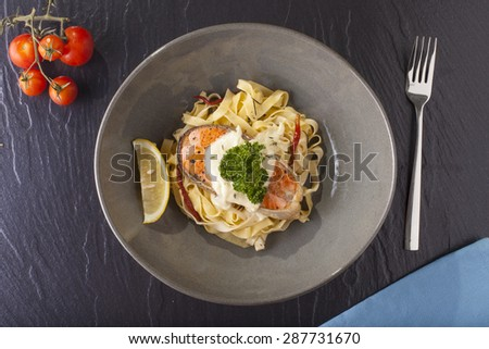 Pasta salmon, fresh seasoning pasta with grilled salmon steak in a decor dish - stock photo