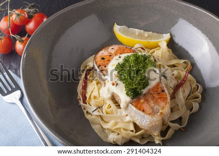 Pasta salmon fresh seasoning pasta with grilled salmon steak in a decor dish - stock photo