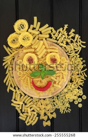 Pasta selection with abstract smiley face on a wooden board over dark wood background.. - stock photo