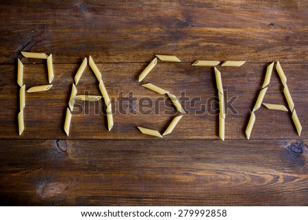 pasta sign made of penne pasta on dark wood rustic table background overhead angle shot - stock photo
