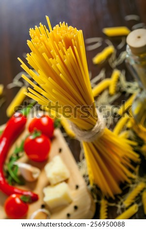 Pasta spaghetti and sauce ingredients on table - stock photo