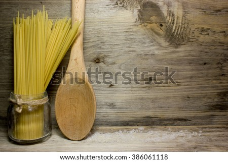 Pasta Spaghetti and wooden spoon on a wooden background - stock photo