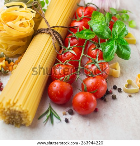 Pasta spaghetti, cherry tomatoes and spices, ingredients for cooking - stock photo
