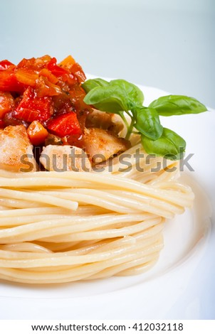 Pasta spaghetti, chicken, sweet and sour sauce topping with basil on white plate - stock photo