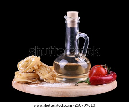 Pasta spaghetti noodles with an olive oil, chili pepper and tomatoes on wooden plate - stock photo