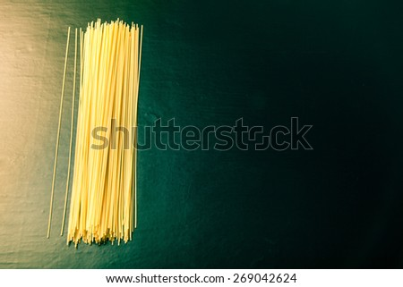 Pasta spaghetti on a black background. Selective focus. Toned. Space for text. - stock photo