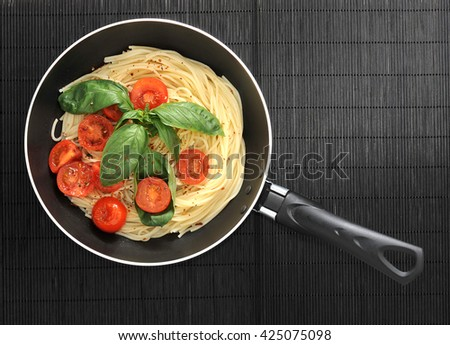 pasta spaghetti with cherry tomatoes and basilikum in the pan. top view - stock photo