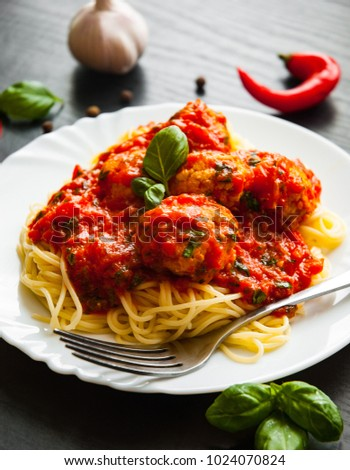 pasta spaghetti with meatballs in tomato sauce on a plate on dark wooden background
