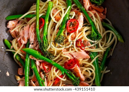 Pasta spaghetti with smoked salmon, chilli and broccoli. in Wok - stock photo
