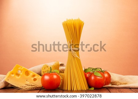 Pasta spaghetti with tomatoes and cheese on a pink background. - stock photo