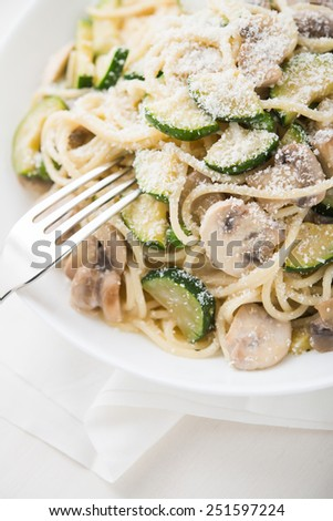 Pasta ( spaghetti ) with zucchini, mushrooms, creamy sauce and parmesan on white background. - stock photo