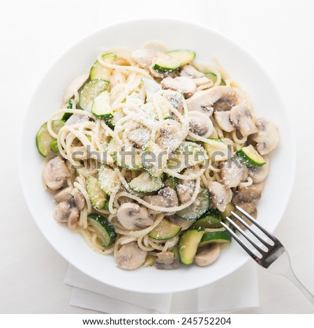 Pasta ( spaghetti ) with zucchini, mushrooms, creamy sauce and parmesan top view. - stock photo