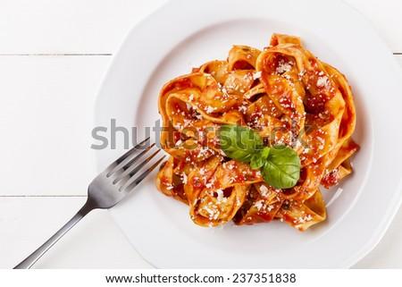 Pasta tagiatelle with tomato on white woodboard - stock photo