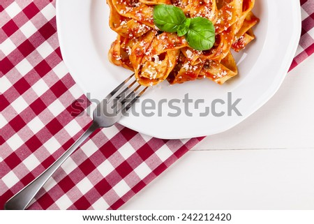Pasta tagiatelle with tomato on white woodboard - stock photo