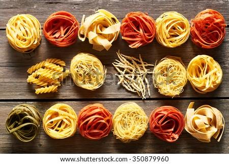 Pasta tagliatelle set over wooden background - stock photo