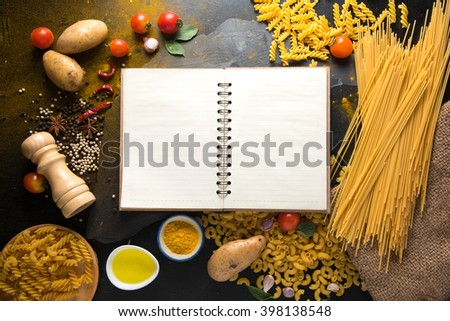 pasta tagliatelle with tomatoes, vegetables and spices for tomato sauce,notebook on dark background, top view - stock photo