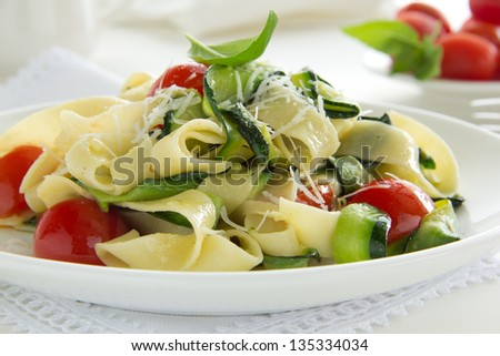Pasta tagliatelle with zucchini and tomatoes. - stock photo