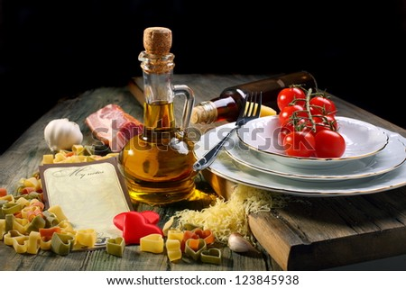 Pasta, tomato, oil and plates on a wooden table.