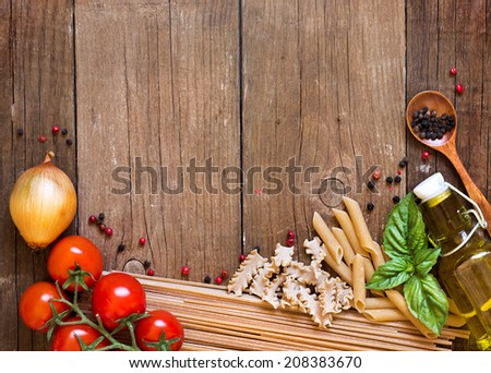 Pasta, tomatoes, onion, olive oil and basil on wooden background - stock photo