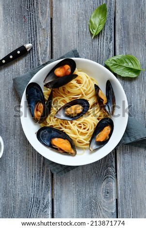 Pasta topped with mussels and basil, top view - stock photo
