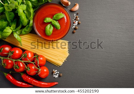 Pasta, vegetables, herbs and spices for Italian food on black slate background, top view - stock photo