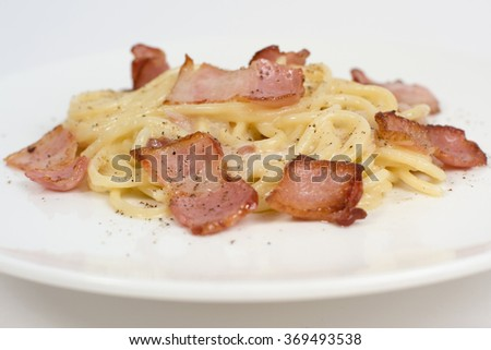 Pasta with bacon and mint on white plate - stock photo