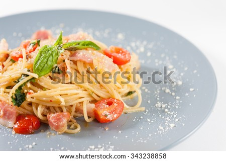 Pasta with bacon and tomato in grey ceramic dish. - stock photo